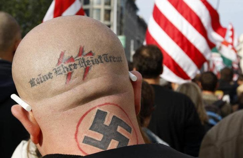 "A neo Nazi attends a rally in Budapest October 23, 2009. The words, the motto of the S.S., read ""my honor is my loyalty"" (photo credit: LASZIO BALOGH/REUTERS)"