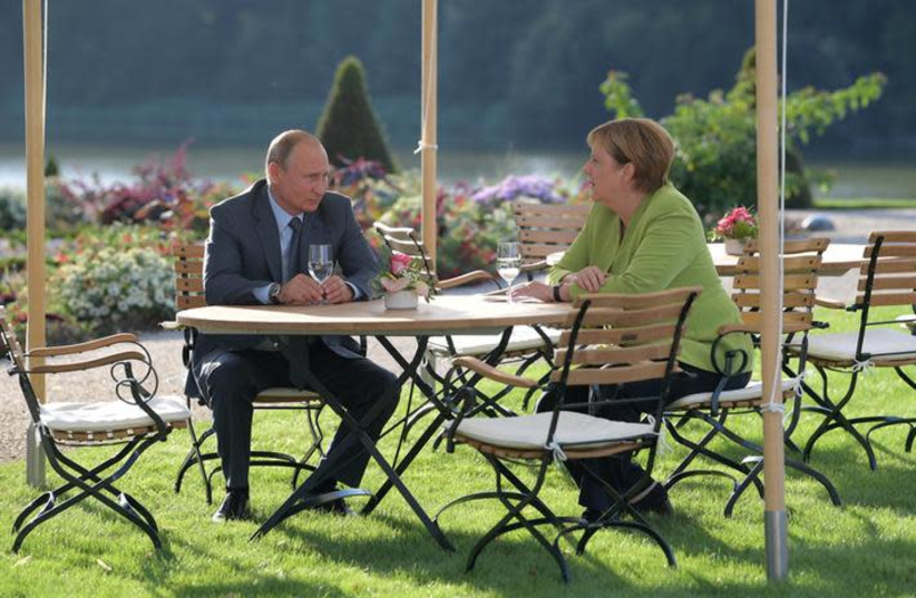 German Chancellor Angela Merkel and Russian President Vladimir Putin speak during their meeting at the German government guest house Meseberg Palace in Gransee, Germany August 18, 2018 (photo credit: SPUTNIK PHOTO AGENCY / REUTERS)