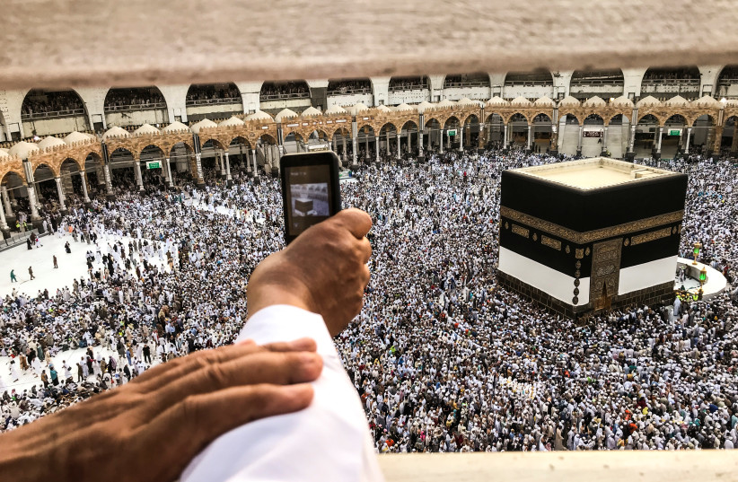 A muslim pilgrim takes a video with his mobile phone while others circle the Kaaba and pray at the Grand mosque ahead of annual Haj pilgrimage in the holy city of Mecca, Saudi Arabia August 16, 2018 (photo credit: ZOHRA BENSEMRA/REUTERS)