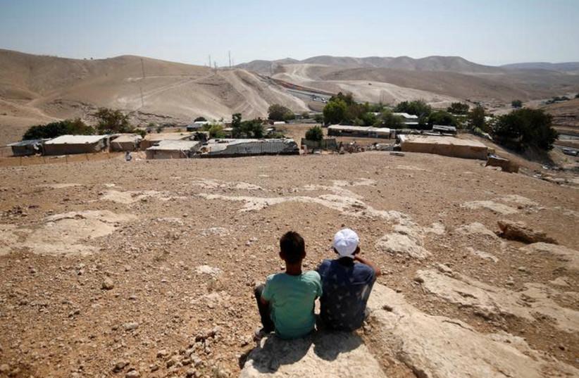 Palestinian boys sit in the Bedouin village of al-Khan al-Ahmar near Jericho in the West Bank July 5, 2018 (photo credit: REUTERS/MOHAMAD TOROKMAN)