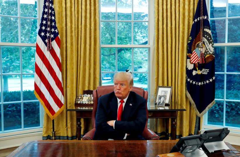US President Donald Trump reacts to a question during an interview with Reuters in the Oval Office of the White House in Washington, US, August 20, 2018 (photo credit: LEAH MILLIS/REUTERS)