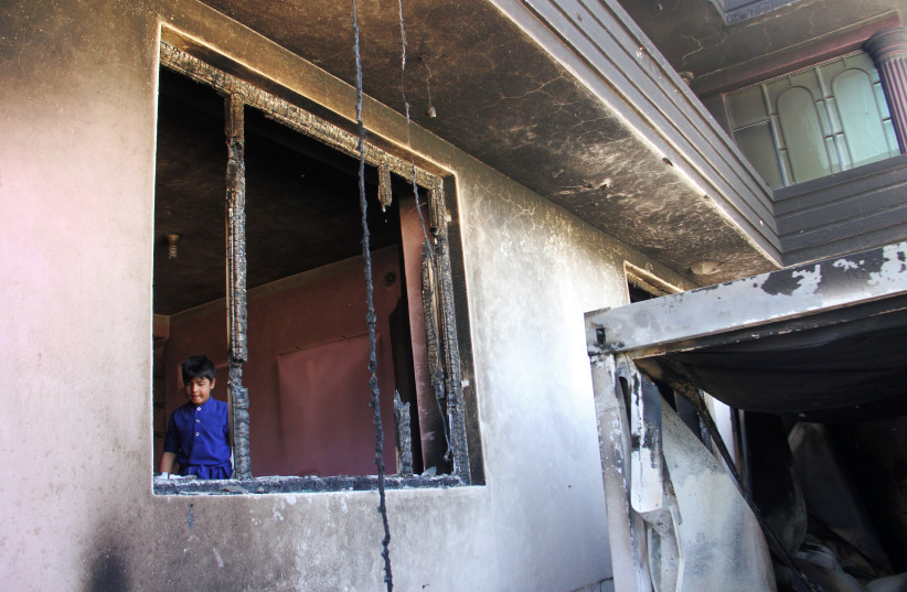 An Afghan boy is seen inside a burnt building after a Taliban attack in Ghazni city, Afghanistan August 15, 2018. (photo credit: REUTERS/MUSTAFA ANDALEB)