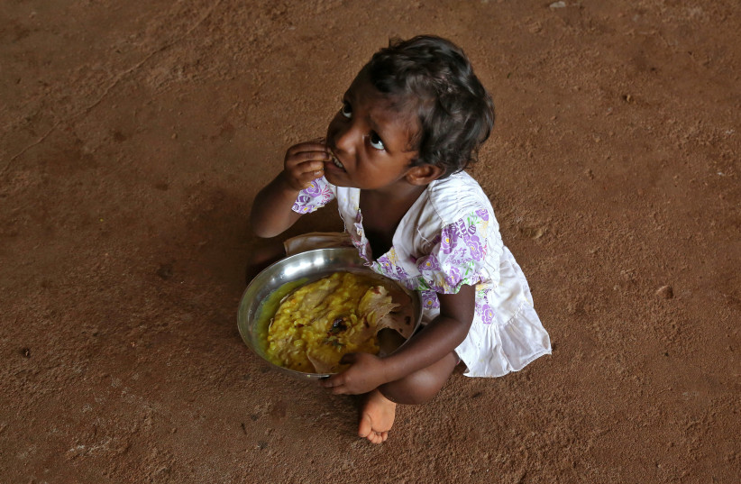 A flood-affected girl eats her food inside a school, which has been converted into a temporary relief camp, in Kochi in the southern state of Kerala, India, August 20, 2018.  (photo credit: REUTERS/SIVARAM V)