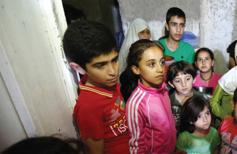 CHILDREN WAIT for meals provided through the initiative Family Kitchen, in the Al-Baqaa Palestinian refugee camp near Amman, Jordan, on June 11 (photo credit: REUTERS)
