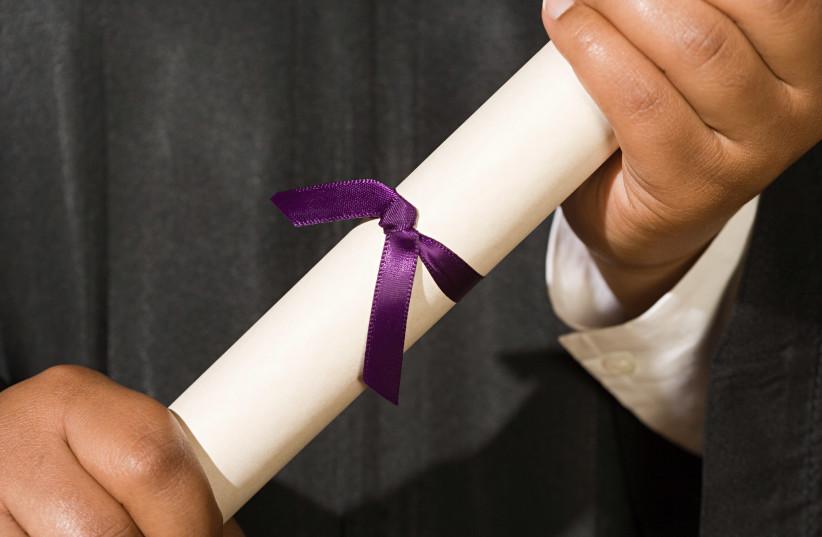 Graduate holding diploma [illustrative] (photo credit: INGIMAGE)