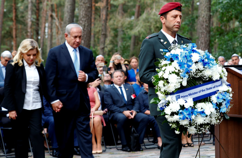 Prime Minister Benjamin Netanyahu and his wife Sara Netanyahu attend the commemoration of victims and award ceremony of the Righteous Among the Nations at the Paneriai Memorial in Vilnius, Lithuania August 24, 2018. (photo credit: INTS KALNINS / REUTERS)