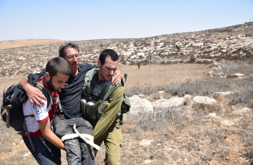 Left-wing activist evacuated after confrontation with settlers, Aug 25, 2018 (photo credit: NASSR NAWAJ'AH B'TSELEM)