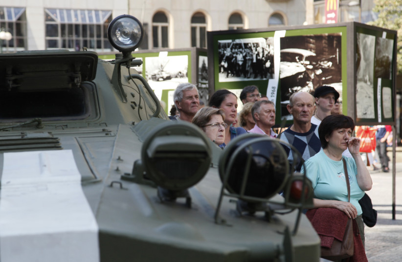 People stand near a Soviet-made military vehicle as they watch a documentary on the Soviet Union-led occupation by the Warsaw Pact armies to halt former Czechoslovak Communist Party leader Alexander Dubcek's Prague Spring political liberalisation reforms in then Czechoslovakia, broadcasted on a disp (photo credit: PETR JOSEK / REUTERS)