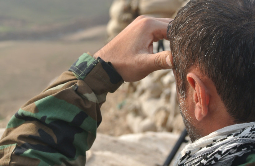 A PAK member looks out over a frontline during the war on ISIS in Iraq in 2016. (photo credit: SETH J. FRANTZMAN)