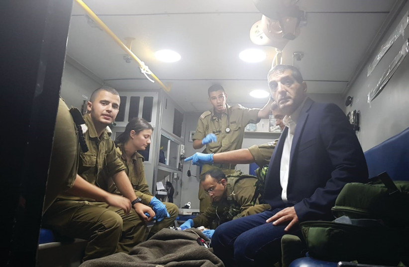 SHEBA MEDICAL CENTER Director General, Prof. Yitshak Kreiss and IDF combat medics transport a severely wounded Syrian child to Sheba Medical Center (photo credit: COURTESY - SHEBA MEDICAL CENTER)