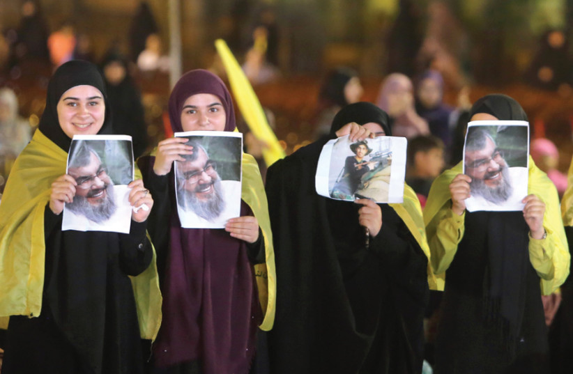 FEMALE SUPPORTERS display pictures of Hezbollah leader Sayyed Hassan Nasrallah as he remotely delivers an address, in Beirut on August 14. (photo credit: REUTERS)