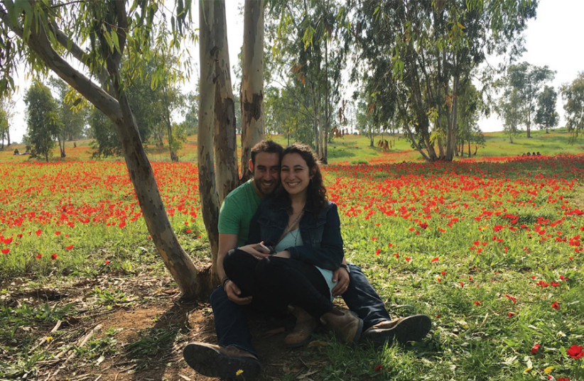 THE WRITER'S daughter Merav and husband, Gabe, at the Darom Adom festival in February – about a month before the protests along the Gaza border started. Today, where the picture captured the beautiful red anemones, it's all burned fields because of the fire kites. (photo credit: BRIAN BLUM)