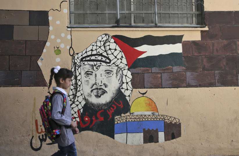 A child walks in front of a mural painting depicting the late Palestinian leader Yasser Arafat on her way to a school run by United Nations Agency for Palestinian Refugees (UNRWA) in Balata refugee camp, east of Nablus on August 29, 2018 (photo credit: JAAFAR ASHTIYEH / AFP)