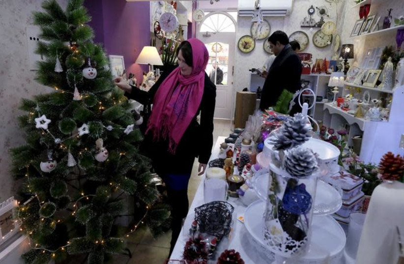 An Iranian Christian woman looks at a Christmas tree at a shop in central Tehran December 23, 2015 (photo credit: RAHEB HOMAVANDI/TIMA VIA REUTERS)