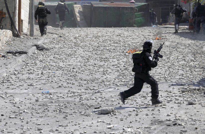 An Israeli soldier runs during clashes in the West Bank (photo credit: REUTERS)