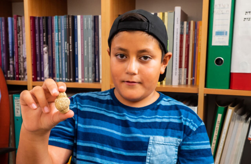 Itamar Berna and the 11,500-year-old figurine (photo credit: ASAF PERETZ/ISRAEL ANTIQUITIES AUTHORITY)