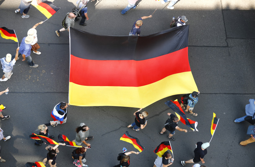 Supporters of the Anti-immigration party Alternative for Germany (AfD) hold German flags during a protest in Berlin, Germany May 27, 2018 (photo credit: REUTERS/HANNIBAL HANSCHKE)