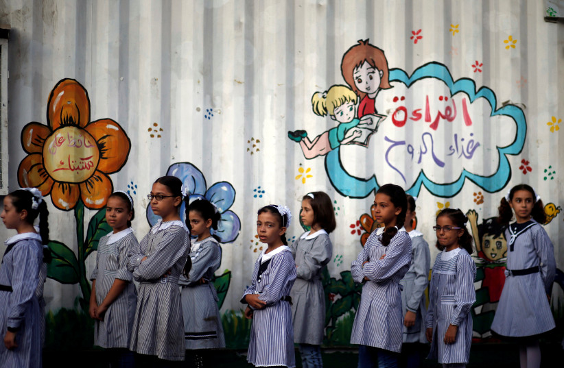 Palestinian schoolgirls queue at an UNRWA-run school, on the first day of a new school year, in Gaza City August 29, 2018 (photo credit: REUTERS/MOHAMMED SALEM)