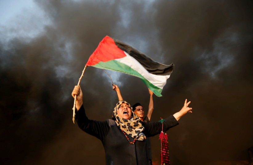 A Palestinian woman shouts slogans during a March of Return protest at the border fence between Israel and Gaza, east of Gaza City August 31, 2018.  (photo credit: MOHAMMED SALEM/ REUTERS)