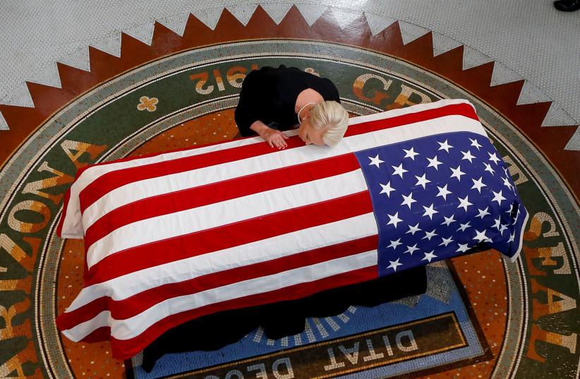 Cindy McCain, wife of U.S. Senator John McCain, touches the casket during a memorial service at the Arizona Capitol in Phoenix, Arizona, U.S., August 29, 2018. (photo credit: REUTERS)