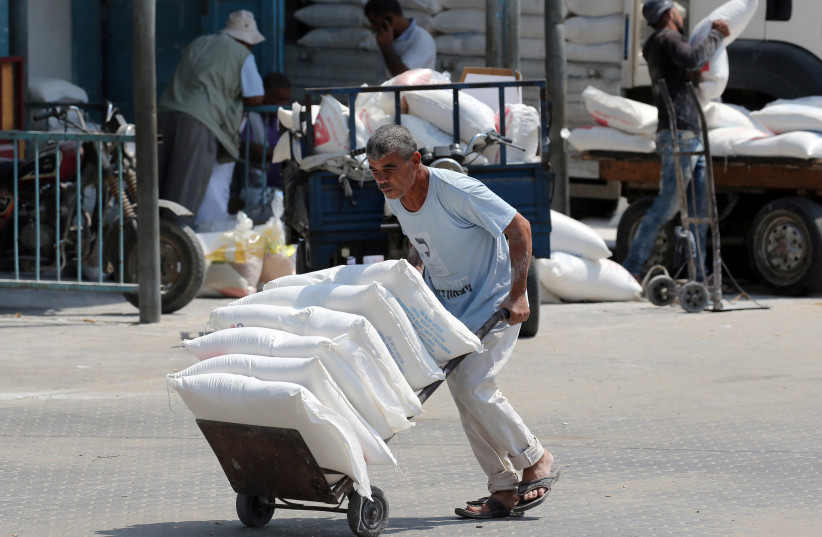 A Palestinian man pushes a cart with bags of flour at an aid distribution center run by United Nations Relief and Works Agency (UNRWA) in Khan Younis in the southern Gaza Strip September 1, 2018. (photo credit: REUTERS/IBRAHEEM ABU MUSTAFA)