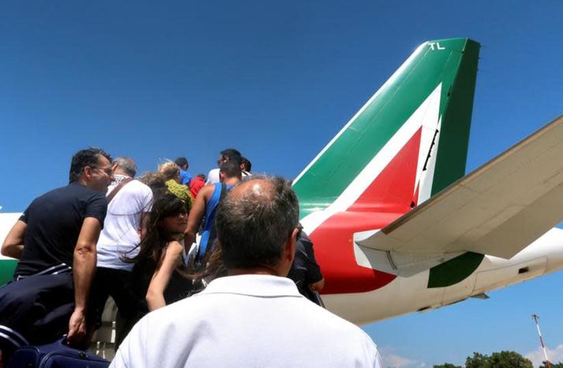 Passengers board an Alitalia airplane at Cagliari airport, Italy, July 9, 2018 (photo credit: STEFANO RELLANDINI/ REUTERS/ FILE PHOTO)