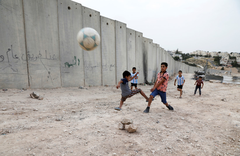 Nassim Ammour, 11, scores a goal as he plays with friends next to the Israeli barrier in the Shuafat refugee camp in east Jerusalem, May 4, 2018 (photo credit: AMMAR AWAD/REUTERS)