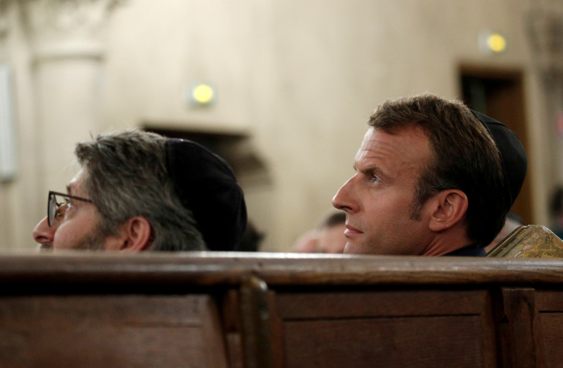 French President Emmanuel Macron (R) and Chief Rabbi of France Haim Korsia (L) listen to speeches during a ceremony that marks the Jewish New Year (Rosh Hashana) at the Great Synagogue in Paris, France, September 4, 2018. (photo credit: YOAN VALAT/POOL VIA REUTERS)