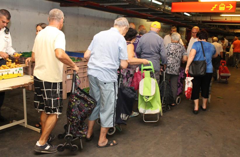 Elderly Israelis receiving aid at a Pitchon Lev assistance center (photo credit: YAKI ZIMERMAN)