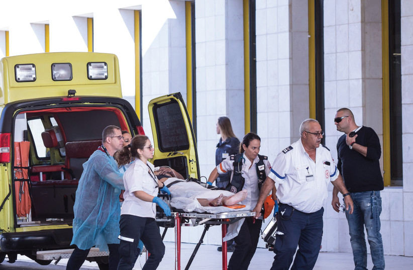 Assuta staff rush a patient to the hospital through its emergency entrance (photo credit: ODED KARNI)