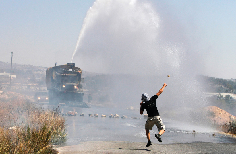 A PALESTINIAN demonstrator hurls a stone as an Israeli truck fires a water cannon during clashes in the West Bank in 2012. (photo credit: REUTERS)