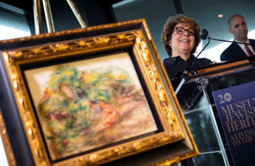 Sylvie Sulitzer speaks next to the painting Deux Femmes Dans Un Jardin by Pierre Auguste Renoir during a ceremony to return the painting, stolen by the Nazis in World War II from Ms. Sulitzer's family, at the Jewish Heritage Museum in New York City, New York, U.S., September 12, 2018. (photo credit: MIKE SEGAR / REUTERS)