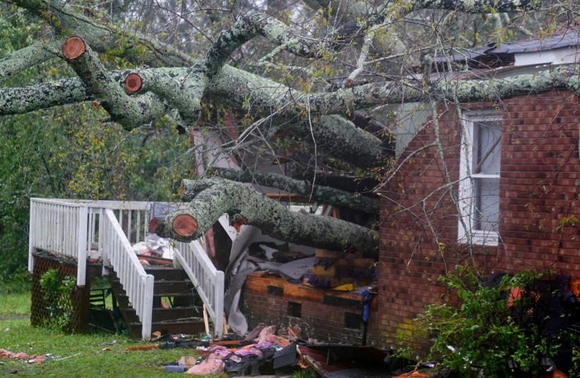 A house where, according to local media, a woman and her child died as a result of a downed tree is pictured as Hurricane Florence comes ashore in Wilmington, North Carolina, U.S., September 14, 2018. (photo credit: CARLO ALLEGRI/REUTERS)