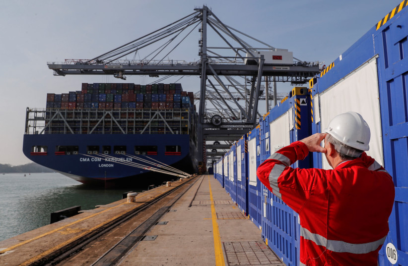 Freight containers are seen on a freight container ship as a worker looks on at DP World, Southampton Docks, in Southampton, Britain, March 27, 2017 (photo credit: REUTERS/EDDIE KEOGH)