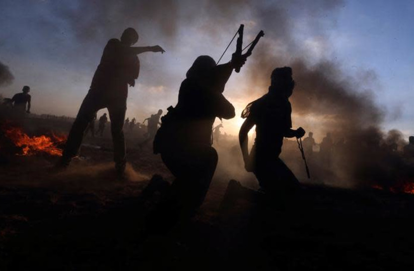 Palestinians hurl stones at Israeli troops during a protest at the Israel-Gaza border fence, in the southern Gaza Strip September 21, 2018 (photo credit: IBRAHEEM ABU MUSTAFA / REUTERS)