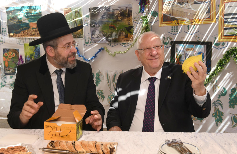 President Reuven Rivlin admires the etrog of Ashkenazi Chief Rabbi David Lau (photo credit: MARK NEIMAN - GPO)
