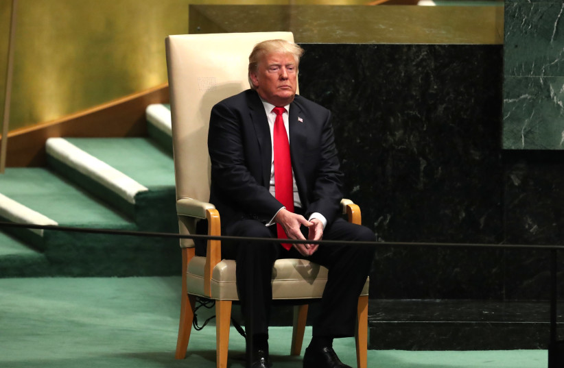 US President Donald Trump sits in the chair reserved for heads of state before delivering his address during the 73rd session of the United Nations General Assembly at UN headquarters in New York, September 25, 2018 (photo credit: CARLO ALLEGRI/REUTERS)