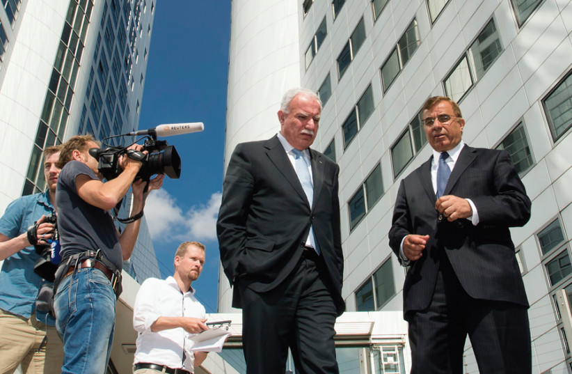 PALESTINIAN FOREIGN MINISTER Riad al-Malki (center) leaves the International Criminal Court at the Hague on August 5, 2014, saying there was 'clear evidence' Israel had committed war crimes in Gaza. (photo credit: Courtesy)