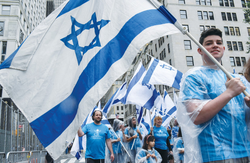 Participants carry Israeli flags at the 'Celebrate Israel'' parade along Fifth Avenue in New York City in 2017 (photo credit: STEPHANIE KEITH/REUTERS)