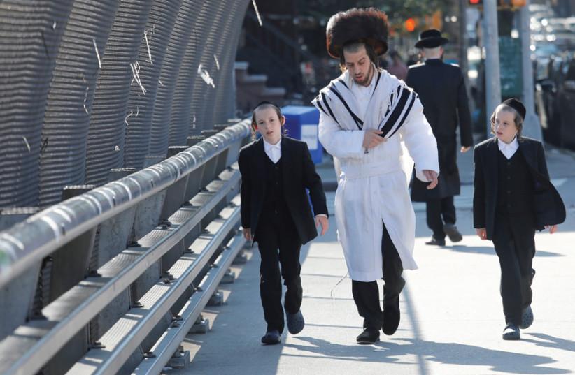 A JEWISH FAMILY walks in Williamsburg, Brooklyn, on Yom Kippur. (photo credit: SHANNON STAPLETON / REUTERS)
