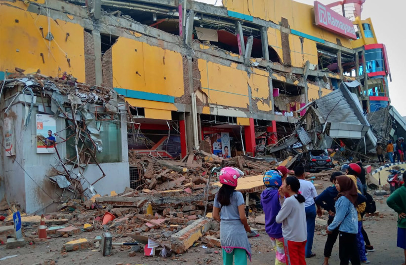 Residents stand in front of a damaged shopping mall after an earthquake hit Palu, Sulawesi Island, Indonesia September 29, 2018. (photo credit: ANTARA FOTO/ROLEX MALAHA VIA REUTERS)