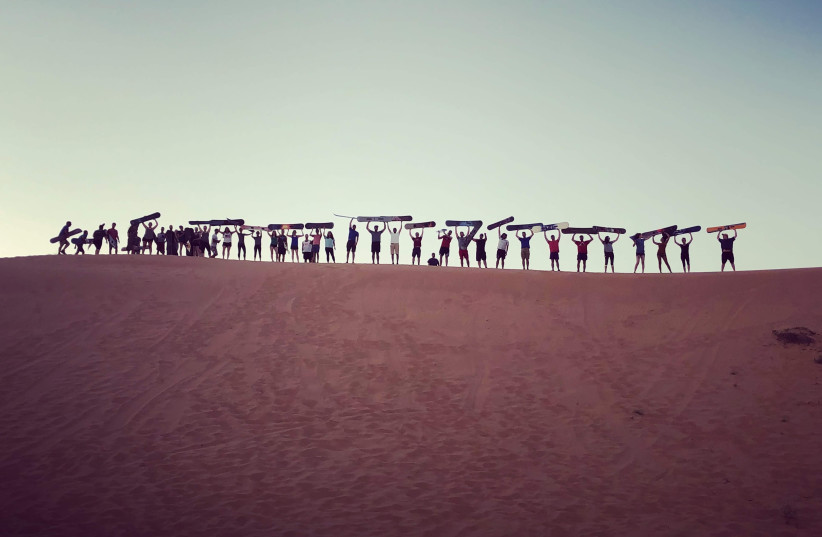 A group of Birthright Israel participants go sandboarding at Dror Bamidbar in the Negev desert. (photo credit: LEAH GRAFF)