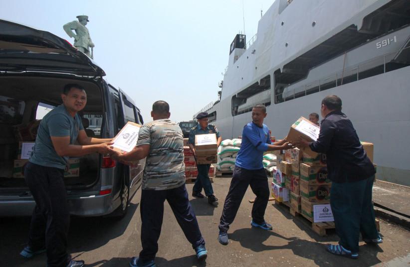 Indonesian navy prepare packages of aid to distribute to victims of the earthquake and tsunami in Palu at Koarmada II port in Surabaya, East Java, Indonesia (photo credit: ANTARA FOTO/DIDIK SUHARTONO/VIA REUTERS)