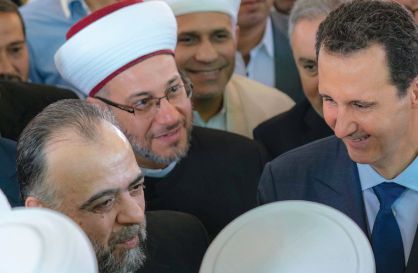 SYRIAN PRESIDENT Bashar Assad greets supporters during Eid al-Adha prayers at a Damascus mosque on August 21. (photo credit: REUTERS)