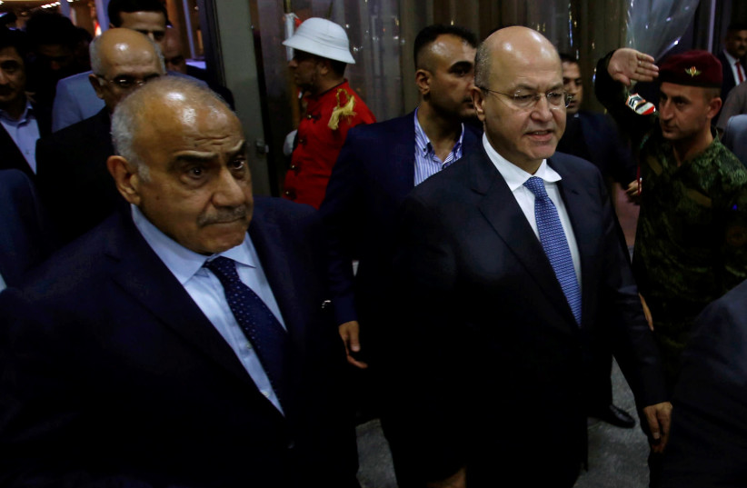 Barham Salih, Iraq's newly elected president, walks with Iraq's new Prime Minister Adel Abdul Mahdi at the parliament headquarters, in Baghdad, Iraq October 2, 2018.  (photo credit: REUTERS/KHALID AL MOUSILY)