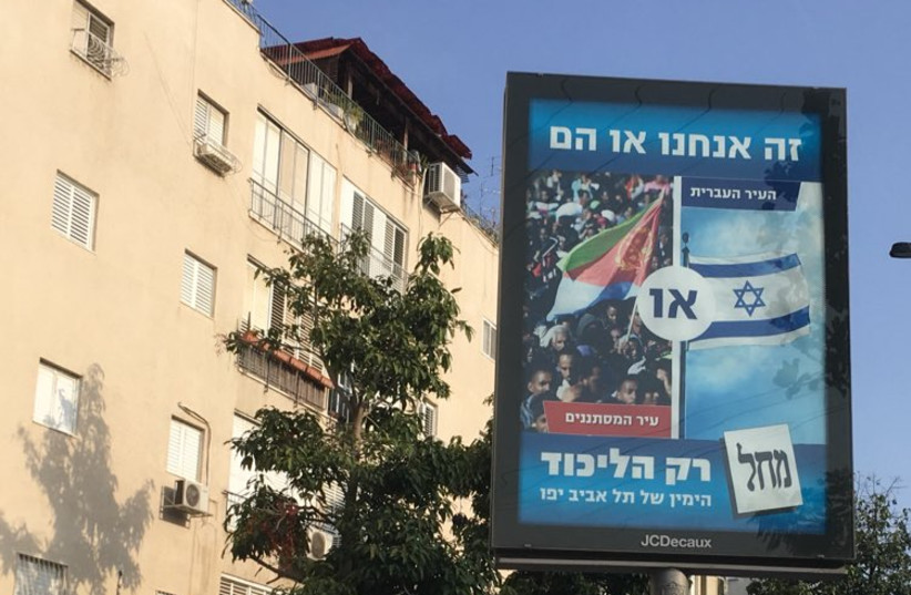 """""""It's us or them - the Hebrew city OR city of infiltrators"""" Likud poster for Tel Aviv elections, October 4, 2018 (photo credit: AVNER GVARYAHU / BREAKING THE SILENCE)"""