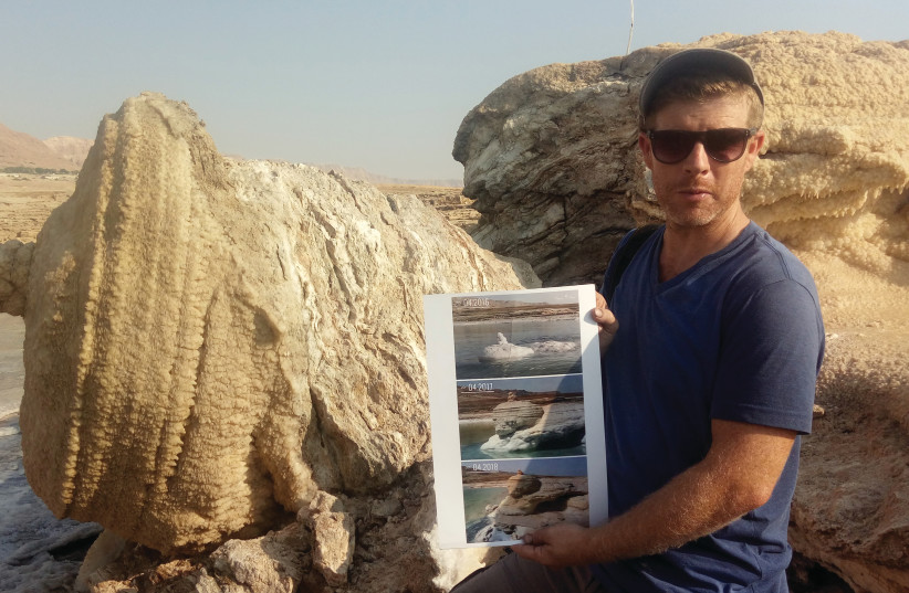 NOAM BEDEIN holds time-lapse images of the emergence of the magnificent salt structure that collapsed last month (photo credit: LIAT COLLINS)
