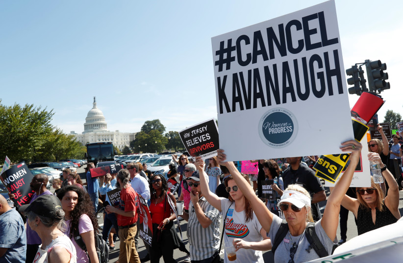 Activists hold a protest march and rally in opposition to U.S. Supreme Court nominee Brett Kavanaugh near the U.S. Capitol in Washington, US, October 4, 2018 (photo credit: KEVIN LAMARQUE/REUTERS)
