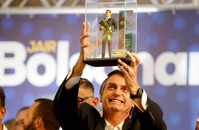 Presidential candidate Jair Bolsonaro, shows a doll of himself during a rally in Curitiba, Brazil March 29, 2018.  (photo credit: REUTERS)