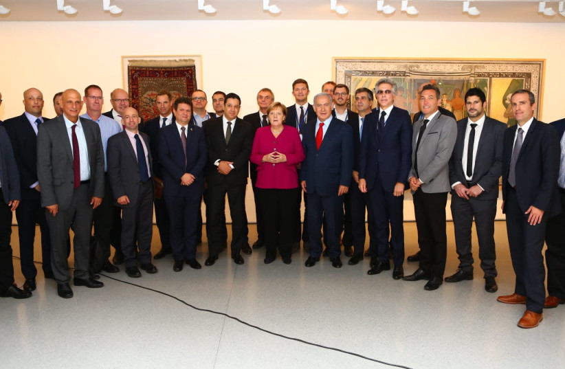 The 'embarrassing' photo of German Chancellor Angela Merkel at an all-male event which inspired Israeli feminists (photo credit: KOBI GIDON / GPO)